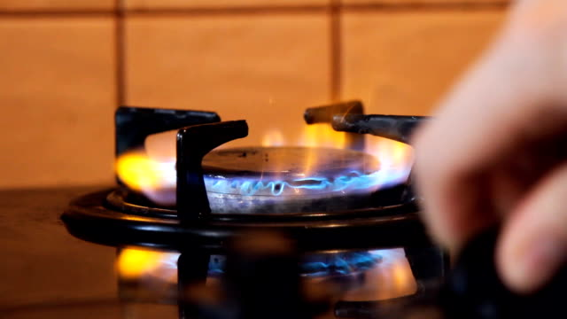 hand opening fire gas burning from a kitchen gas stove