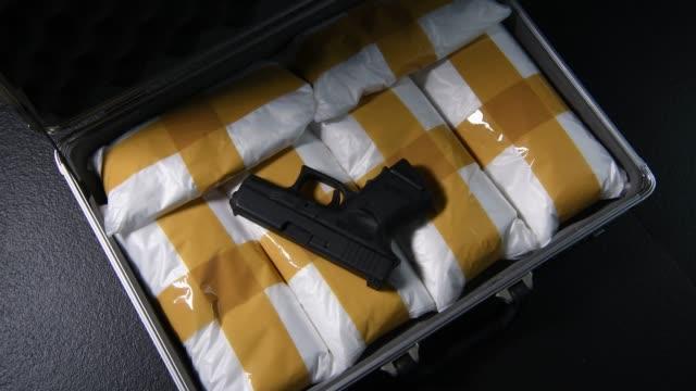 vídeos de stock, filmes e b-roll de uma mão para abrir a mala cheia de drogas narcóticas com uma arma - smuggling