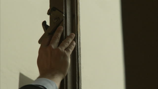 A hand opens the latch of a window in the Haus Wittgenstein to let out some smoke.