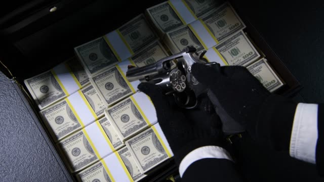 A hand packing money and check the gun