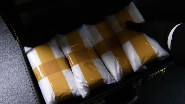 vídeos de stock, filmes e b-roll de uma mão de estupefacientes de embalagem em uma maleta - smuggling