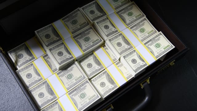 A hand packing of 100 dollar bills in a briefcase