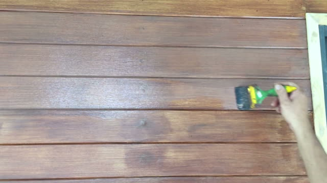 hand painting brown wood protective color on wooden wall - house painting stock videos and b-roll footage