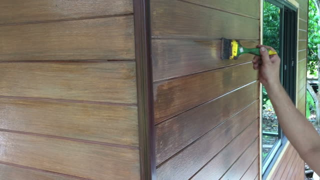 hand painting brown wood protective color on wooden wall - house painter stock videos and b-roll footage