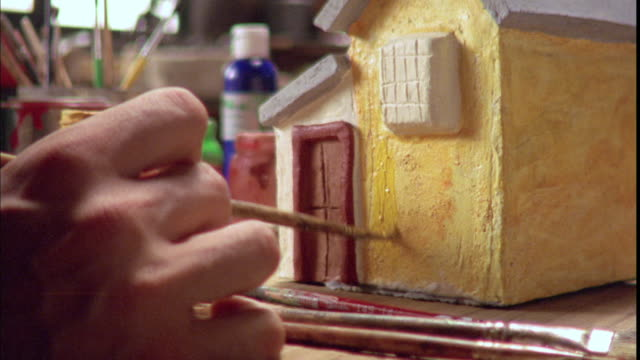 A hand paints a small clay house.