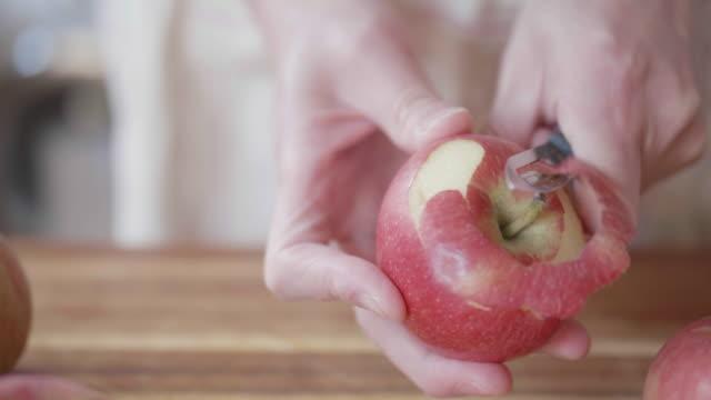 stockvideo's en b-roll-footage met hand peeling appel - schil