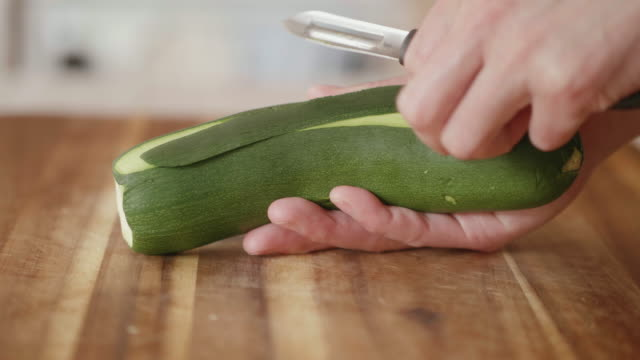 hand peeling courgette ribbon for summer salad - courgette stock videos and b-roll footage