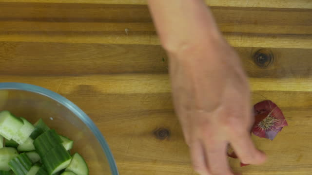 hand peeling red onion on wooden chopping board - red onion stock videos & royalty-free footage