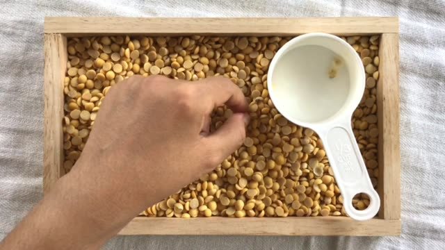 hand peeling soybeans into a measurement cup - dried food stock videos & royalty-free footage