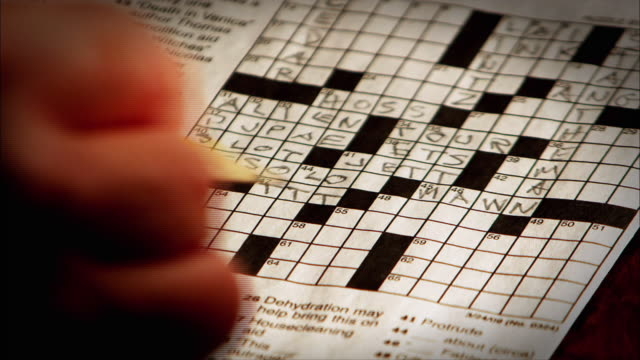 a hand pencils in a word in a crossword puzzle. - crossword stock videos and b-roll footage