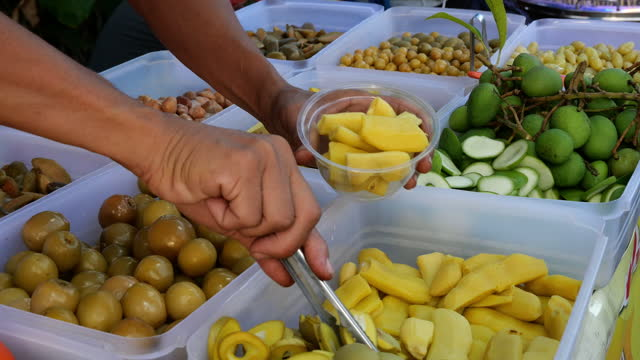 hand pick up pickled fruit for customer,street food in thailand - mango stock videos & royalty-free footage