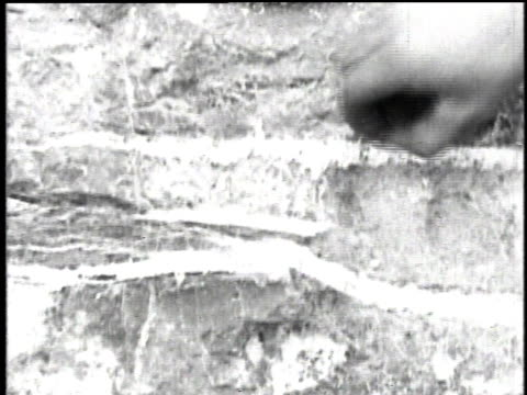 1921 cu hand picking debris from asbestos fibers embedded in natural rock / asbestos, quebec, canada - アスベスト点の映像素材/bロール