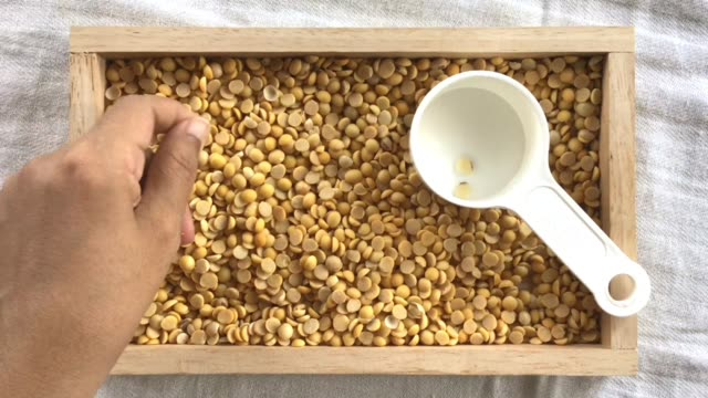 hand picking peel of soybeans into measurement cup - dried food stock videos & royalty-free footage
