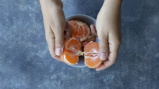 hand picking up a peeled tangerine from fruit bowl - fruit bowl stock videos & royalty-free footage