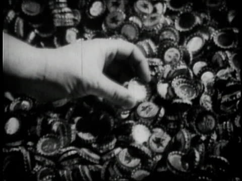 1936 montage hand picking up beer cap from pile / ms beer bottles moving on conveyor belt being capped / - beer cap stock videos & royalty-free footage