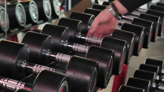 hand picking up dumbbells to workout in gym - arm curl stock videos & royalty-free footage