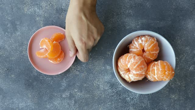 hand picking up plate of  peeled tangerine - fruit bowl stock videos & royalty-free footage