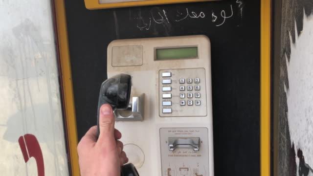 stockvideo's en b-roll-footage met pov hand oppakken van de telefoon in phone booth - telefooncel