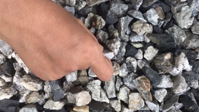 vídeos de stock, filmes e b-roll de mão que escolhe pedras brancas do cascalho da terra - pedra solta