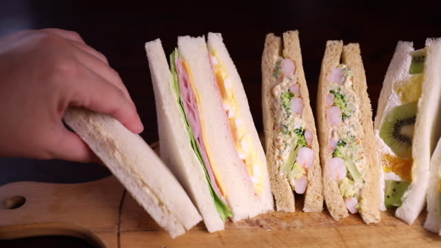 hand picks up a japanese convenience store sandwiches with panning right to left - prawn stock videos & royalty-free footage