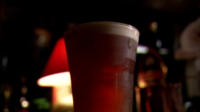 A hand picks up a pint of beer. Available in HD.