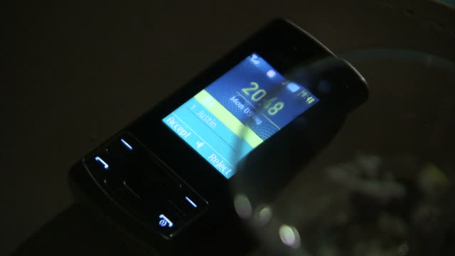 a hand picks up a ringing mobile phone beside a glass. - ring stock videos and b-roll footage