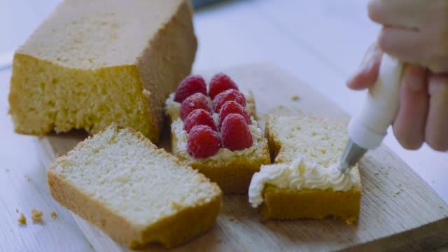 スポンジケーキの上に手のパイピングホイップクリーム - スポンジ点の映像素材/bロール