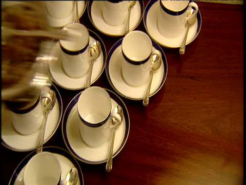 hand places bowl with sugar crystals next to cups and saucers on table - sugar bowl crockery stock videos and b-roll footage
