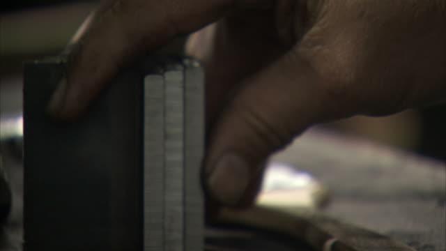 vídeos de stock e filmes b-roll de ecu hand placing bent metal plate next to two other plates - trabalho de metal
