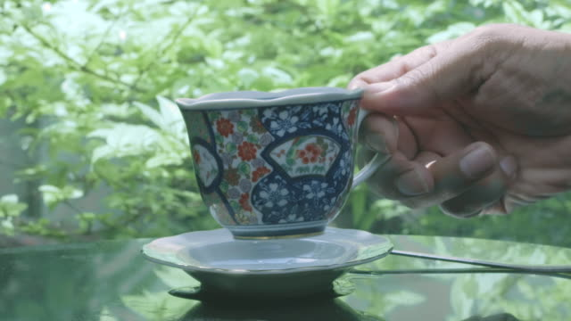 hand placing hot tea cup on saucer over table in nature green background - saucer stock videos & royalty-free footage