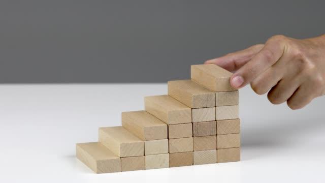 en hand placera sista trä block för att slutföra trappan, som visar tillväxt och förbättring - kloss form bildbanksvideor och videomaterial från bakom kulisserna