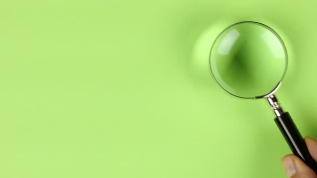 hand placing magnifier glass on bright green background to show search or investigation - magnification stock videos & royalty-free footage
