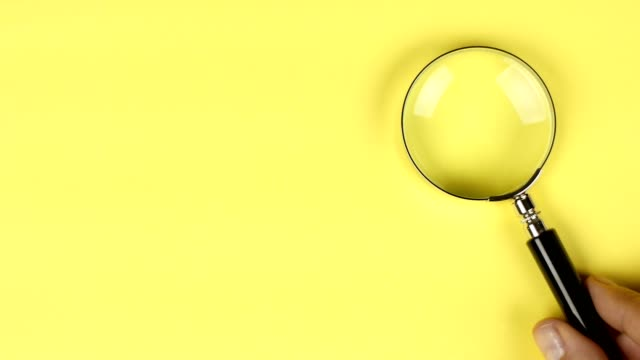 hand placing magnifier glass on yellow background to show search or investigation - magnifying glass stock videos & royalty-free footage
