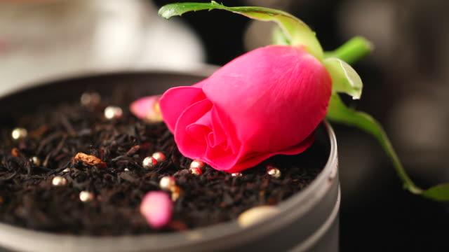 ecu hand placing rose on black tea leaves / seoul, south korea - black tea stock videos and b-roll footage