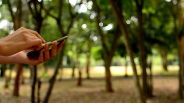vídeos de stock, filmes e b-roll de mão tocando telefone celular - jardim de versailles