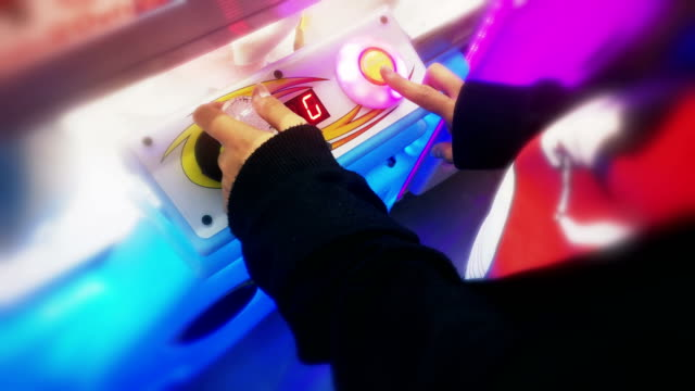 Hand playing with a joystick and button on a crane game machine.