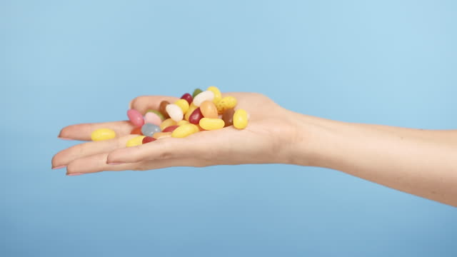 hand playing with candy against blue background - jellybean stock videos & royalty-free footage