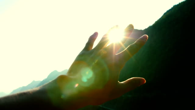 hand playing with sunlight - luminosità video stock e b–roll