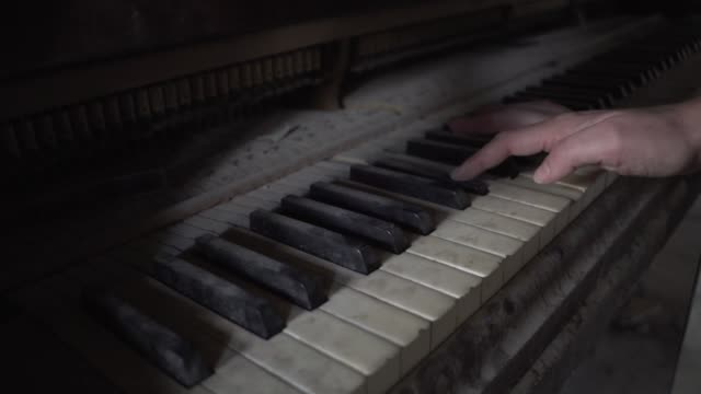 vídeos de stock e filmes b-roll de hand plays dusty old piano in dark room - sujo