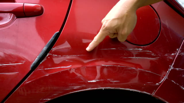 Hand point at scratched of vehicle's paint skin.