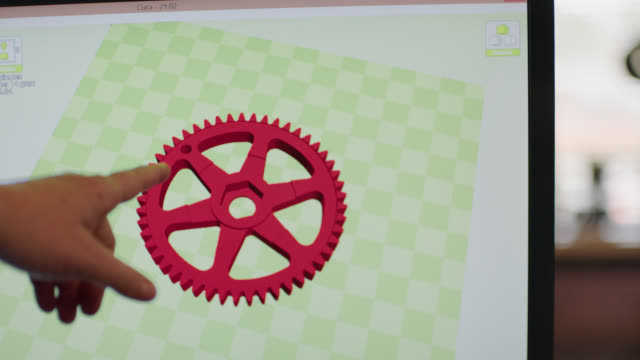 cu. hand points at computer screen as 3d digital model of red gear rotates in graphic design software program. - 3d printing stock videos and b-roll footage