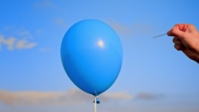 vidéos et rushes de slo mo ld main éclatant un ballon bleu avec une aiguille - ballon de baudruche