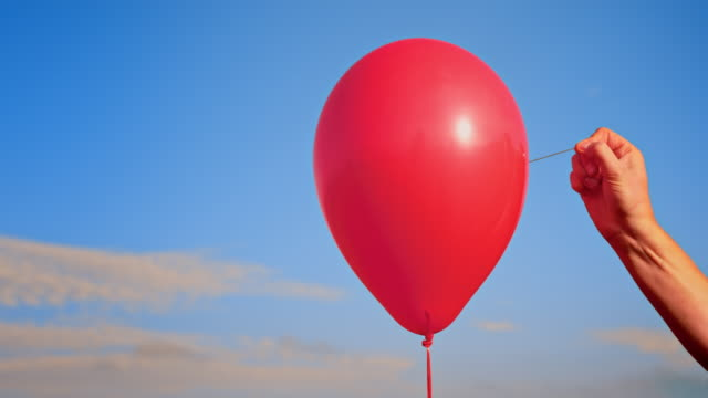 vídeos de stock e filmes b-roll de slo mo ld hand popping a red balloon with a needle - explodir