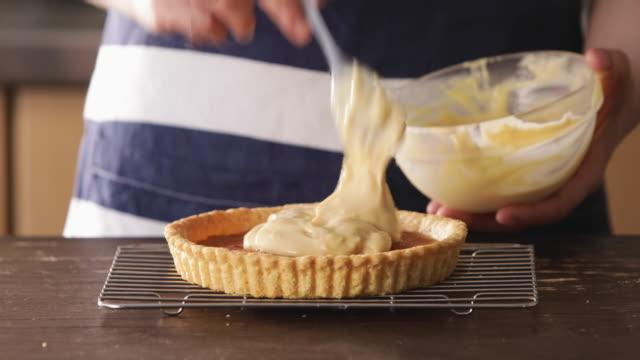 hand pouring custard cream into tartlet dough. - custard stock videos & royalty-free footage