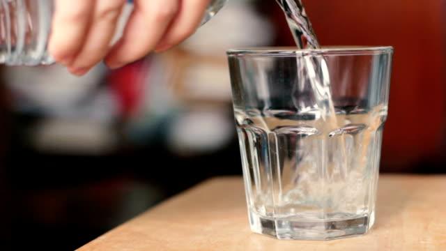 Mano versare acqua potabile in vetro