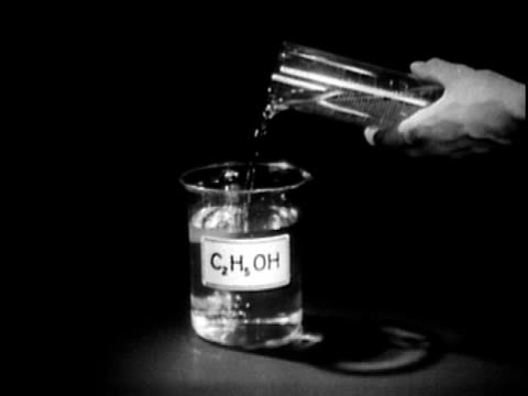 vídeos de stock, filmes e b-roll de 1949 b/w cu hand pouring liquid into beaker labeled c2h5oh, audio - etanol