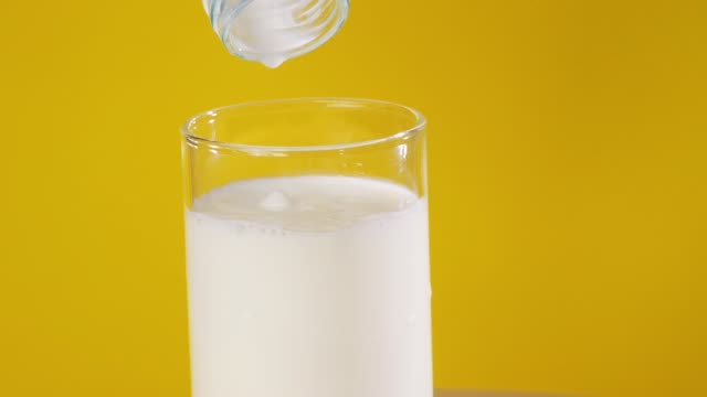 hand pouring milk into glass with yellow background. - buttermilk stock videos & royalty-free footage