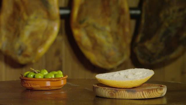 vídeos de stock e filmes b-roll de cu hand pouring olive oil on white bread - pão