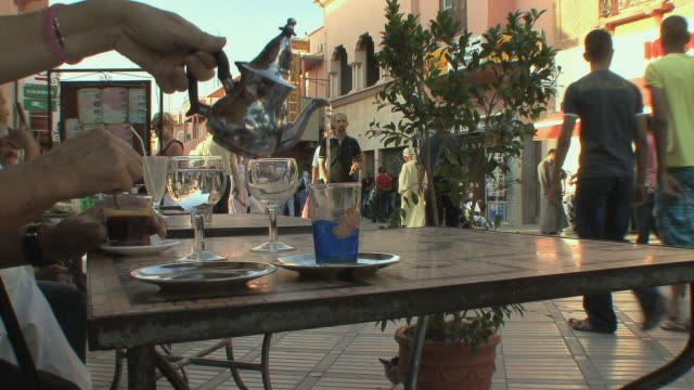 ms hand pouring tea in front of crowded street, marrakech, morocco - food and drink stock videos & royalty-free footage