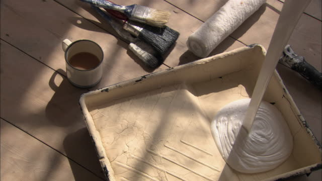 Hand pouring white paint into paint tray and spreading out with paint roller